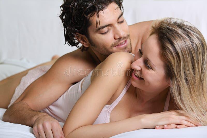 Радостные пары усмехаясь и счастливые в кровати стоковые изображения rf