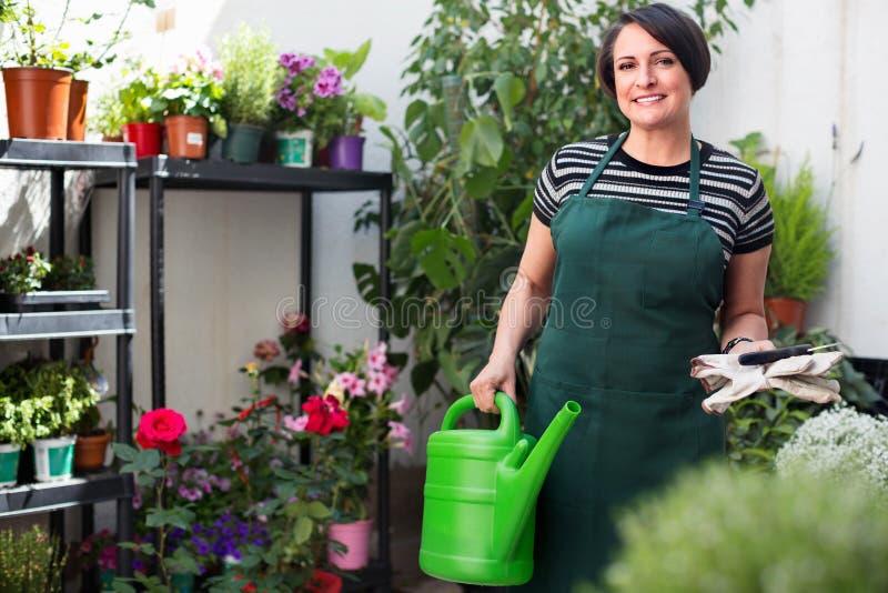 Радостный зрелый флорист женщины усмехаясь среди заводов стоковая фотография