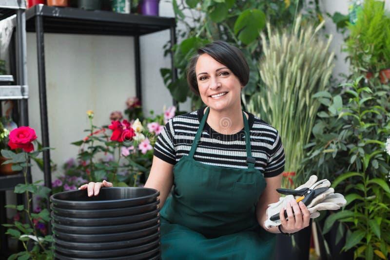 Радостный зрелый флорист женщины усмехаясь среди заводов стоковая фотография rf