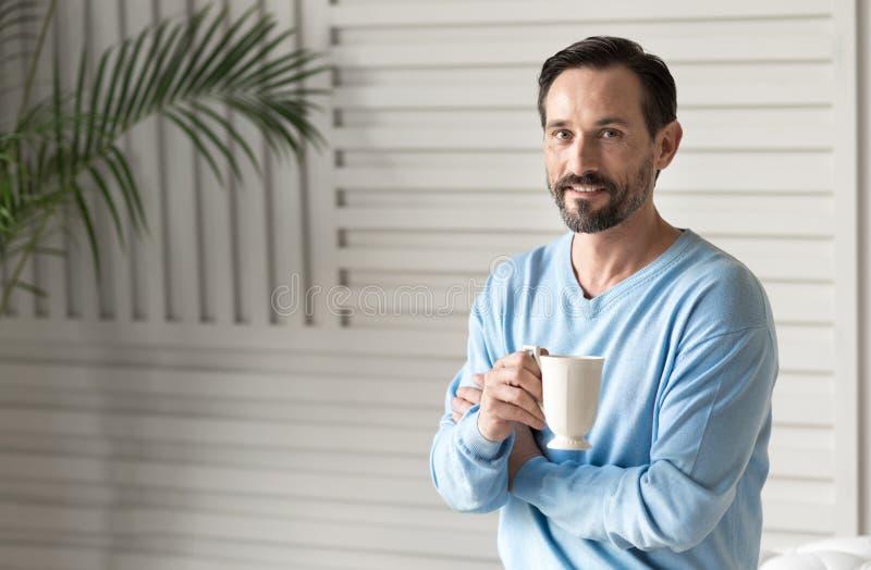 Радостный оптимистический человек держа чашку чая стоковая фотография rf