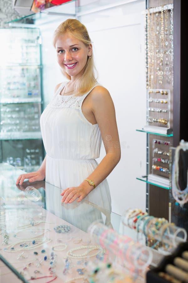 Радостный продавец женщины стоя рядом с стеклянной витриной стоковая фотография rf