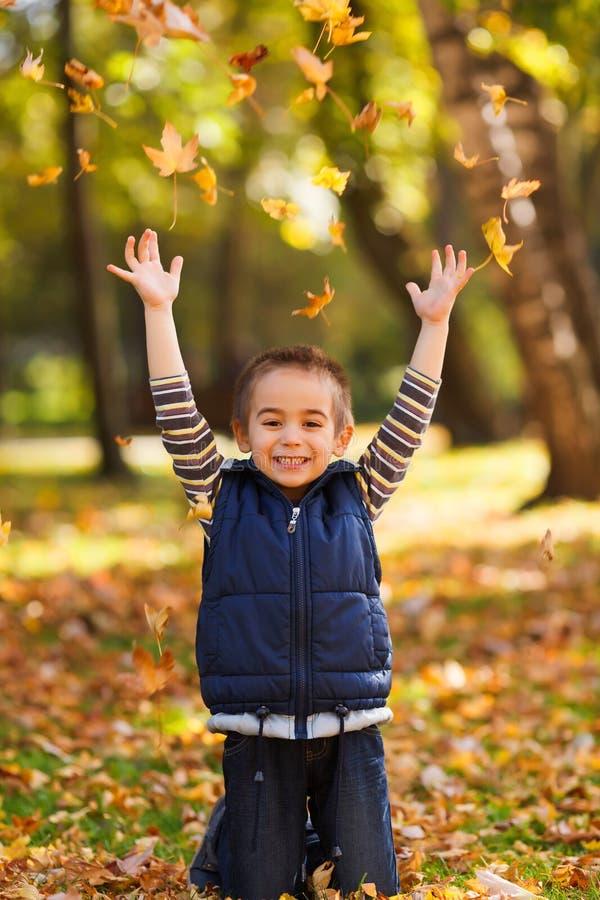 Радостный ребенк играя с листьями стоковое изображение