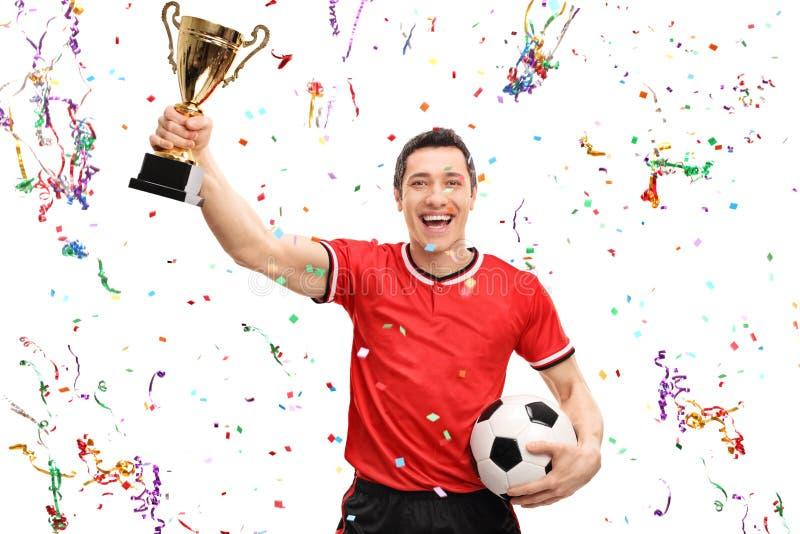 Радостный футболист держа трофей стоковое изображение