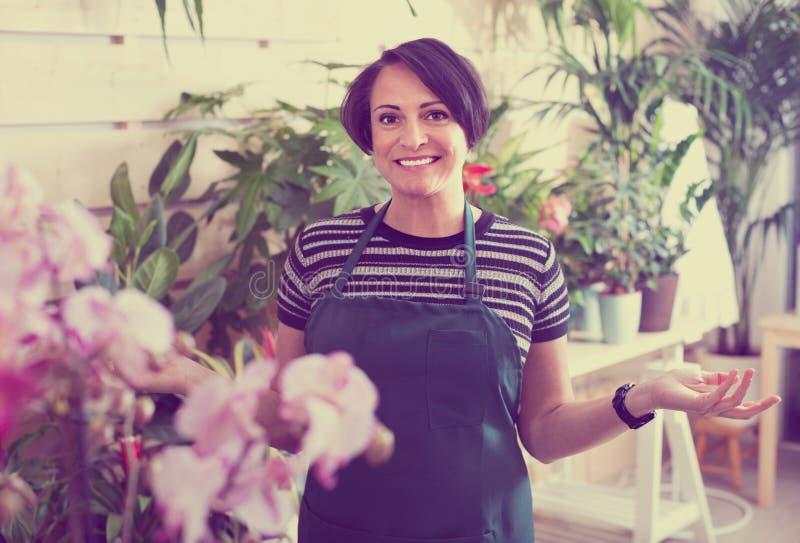 Радостный флорист женщины усмехаясь среди в горшке заводов стоковое фото