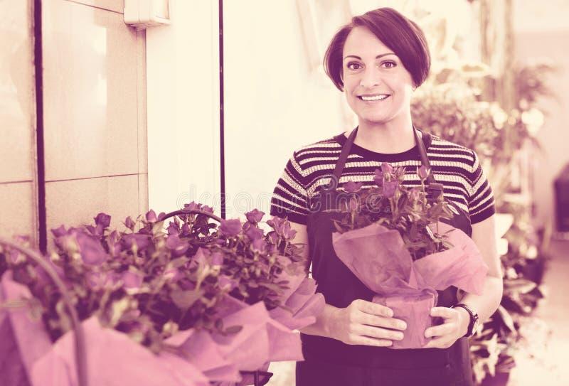 Радостный флорист женщины усмехаясь среди в горшке заводов стоковое фото rf