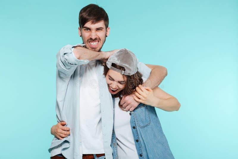 Радостный человек играя и пытая его раздражанную молодую сестру стоковое изображение rf