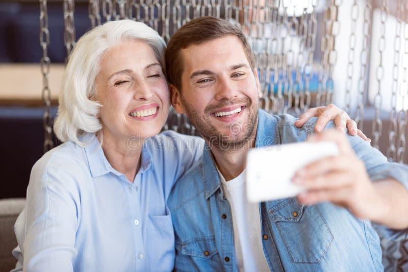 Радостный человек и ее бабушка делая selfies стоковое изображение rf