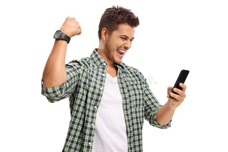 Радостный человек смотря телефон и показывать с его рукой стоковое изображение
