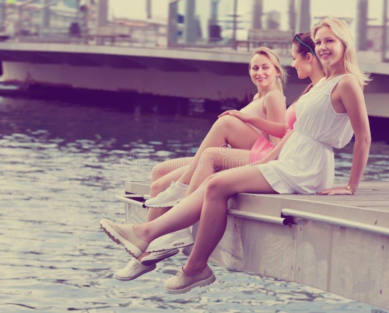 3 радостных девушки сидя на пристани в городке стоковое изображение