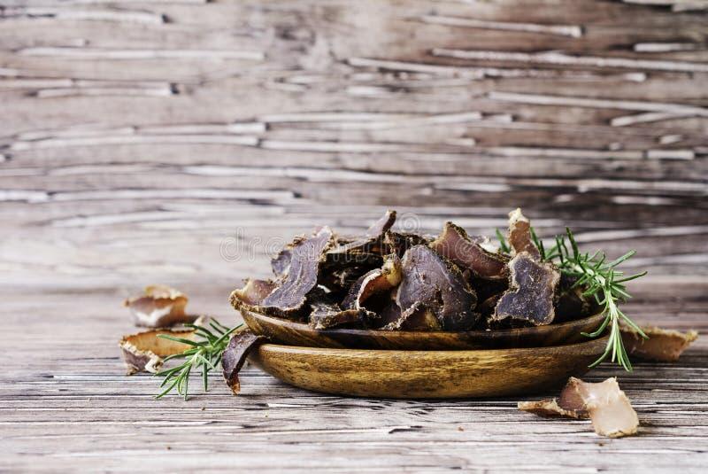 Рванутое мясо, корова, олени, одичалый зверь или biltong в деревянных шарах на деревенской таблице стоковая фотография rf