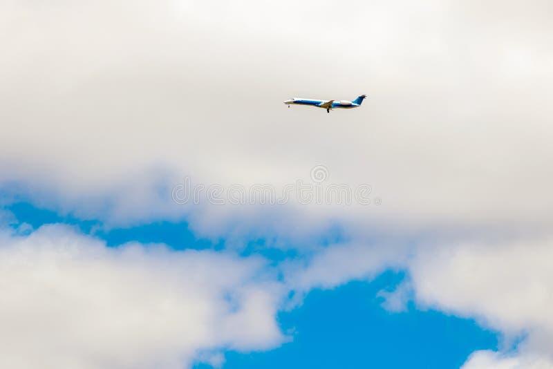 Реактивный самолет летает в облака неба стоковые фото