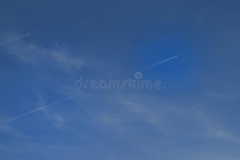 Реактивный самолет прокалывает красивое голубое небо стоковое фото