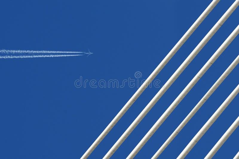 Реактивный самолет с трассировкой & белый мост на голубом небе стоковые изображения rf