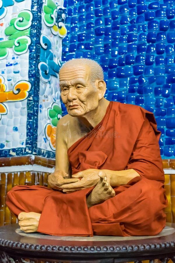 Реалистическая статуя сидя монаха в красной сутане стоковые фотографии rf