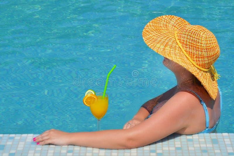 Реальная женская красотка ослабляя в плавательном бассеине стоковые изображения