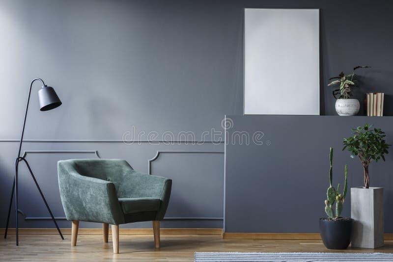 Реальное фото зеленого кресла и черной лампы стоя в сером цвете стоковое фото rf