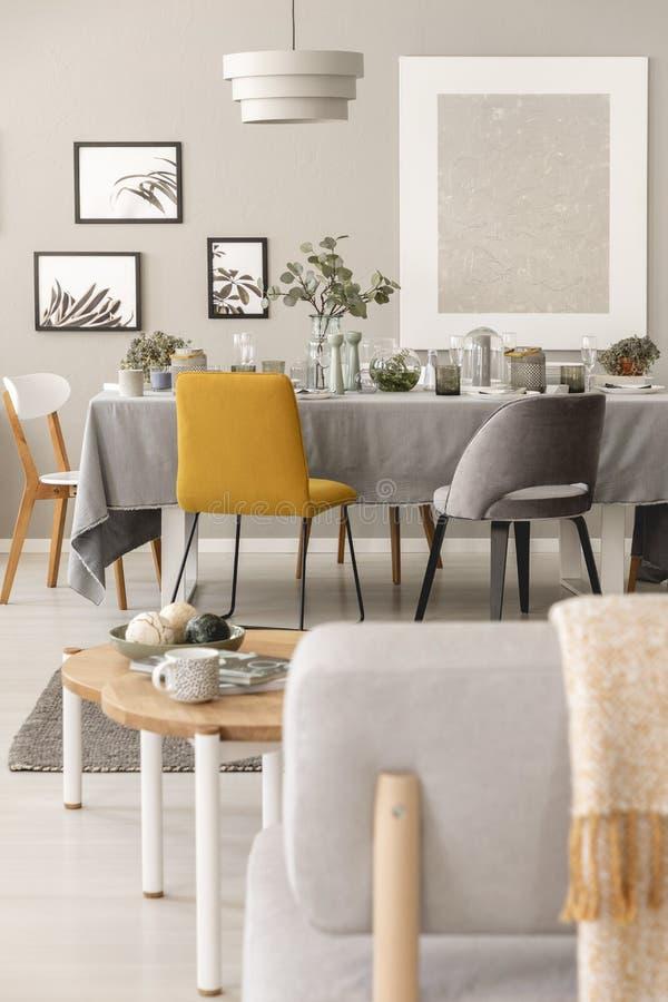 Реальное фото интерьера комнаты обедающего scandi с желтым стулом рядом с таблицей стоковое изображение