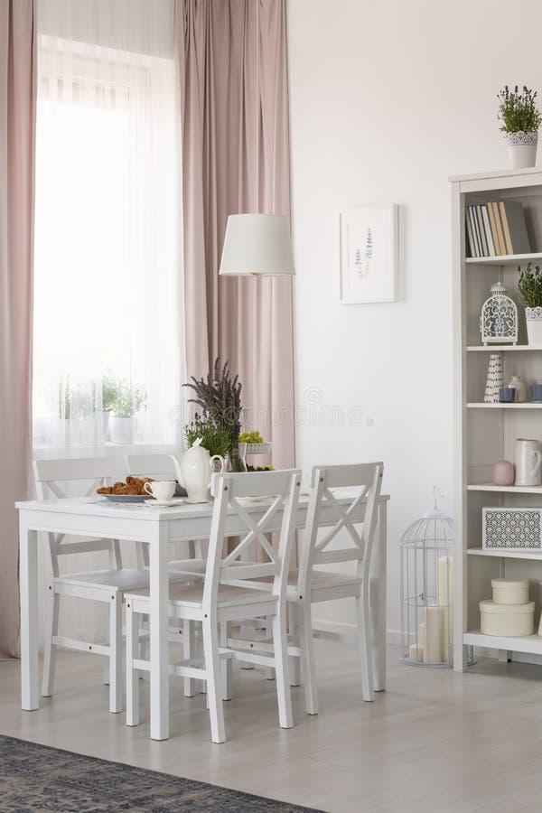 Реальное фото интерьера столовой с стульями и белой таблицы с лавандой и завтраком, окном с задрапировывает и шкаф с оформлением стоковое фото