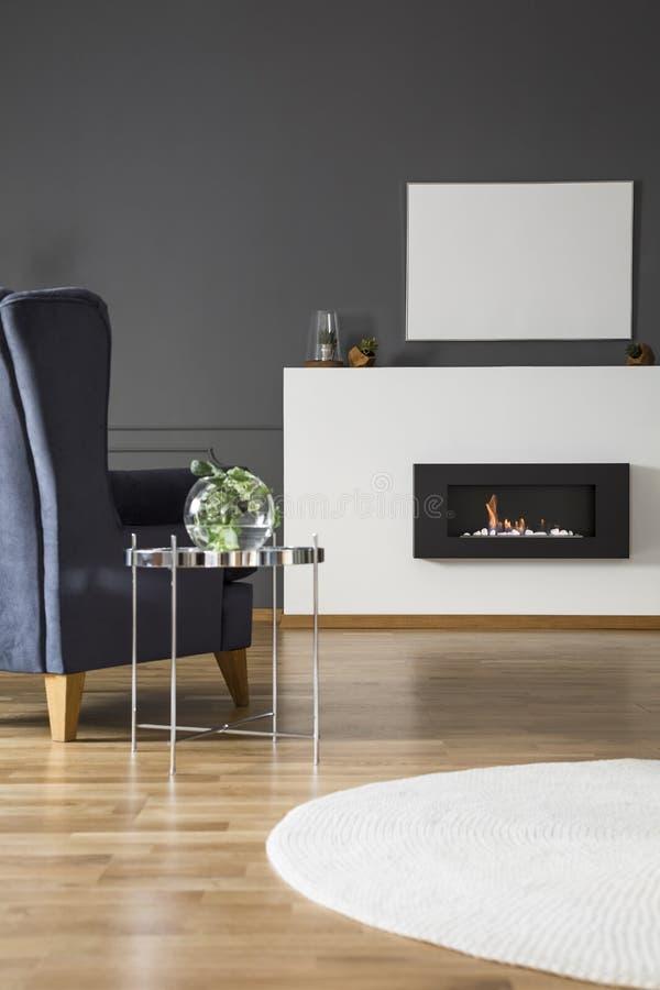 Реальное фото комфортабельного кресла стоя перед био firepl стоковые изображения