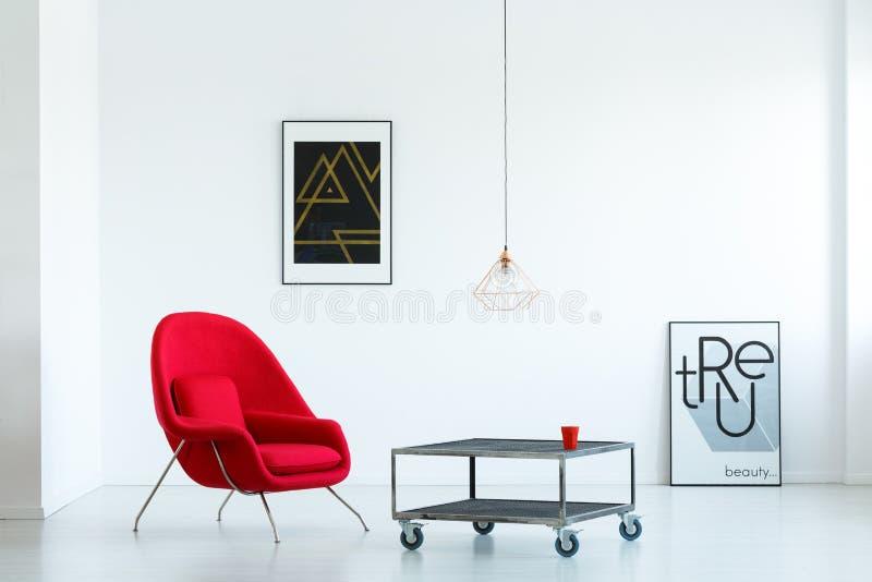 Реальное фото красного кресла стоя рядом с таблицей металла на w стоковая фотография rf