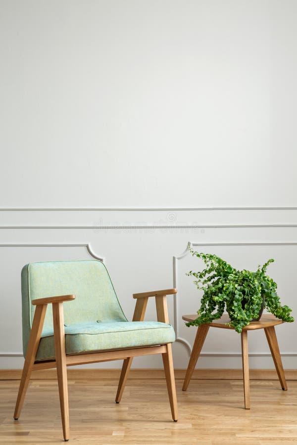 Реальное фото кресла стоя рядом с малой таблицей с a стоковые фотографии rf