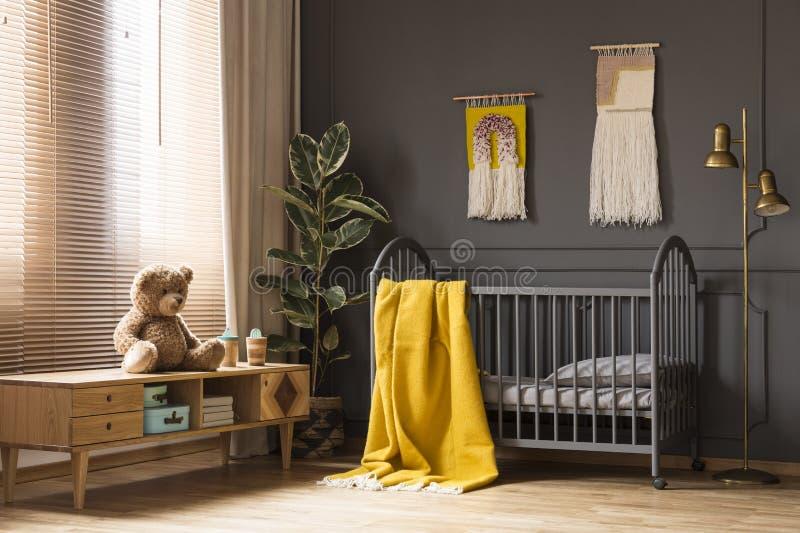 Реальное фото кроватки при желтое одеяло стоя между низким уровнем стоковые изображения