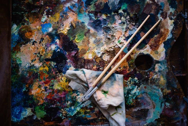 реальное artist& x27; палитра s, краски масла и 2 кисти стоковое изображение rf