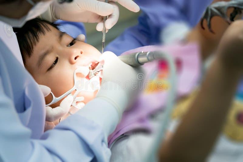 Реальное фото события, милый маленький азиатский мальчик сидя в зубоврачебном ch стоковые фотографии rf