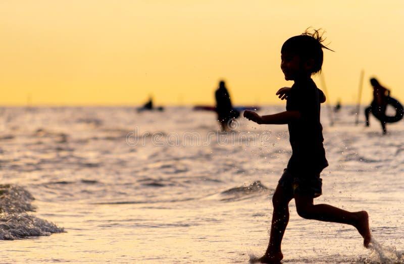 Ребенк бежать на силуэте пляжа песка стоковая фотография rf