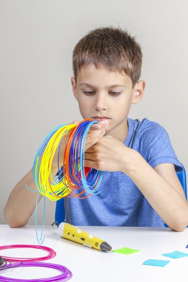 Ребенк держа красочные нити для ручки 3d и выбрать цвет для нового деталя стоковое изображение