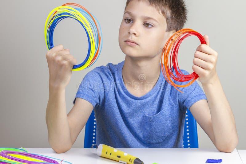 Ребенк держа красочные нити для ручки 3d и выбрать цвет для нового деталя стоковая фотография rf