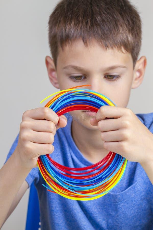 Ребенк держа красочные нити для ручки 3d и выбрать цвет для нового деталя стоковые изображения rf