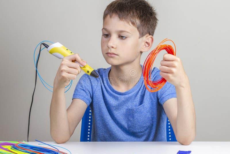 Ребенк держа ручку 3d и красочные нити для ручки 3 d и выбрать цвет для нового деталя стоковое фото rf