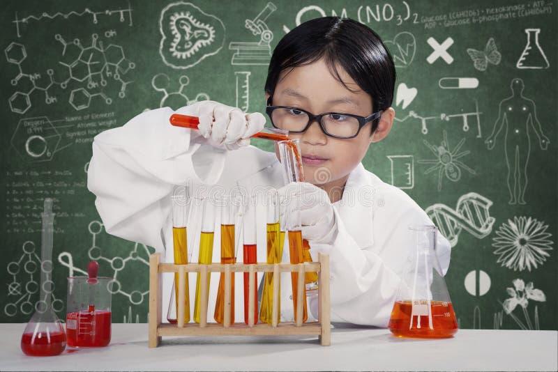 Ребенк делая исследование химии в лаборатории стоковые фотографии rf