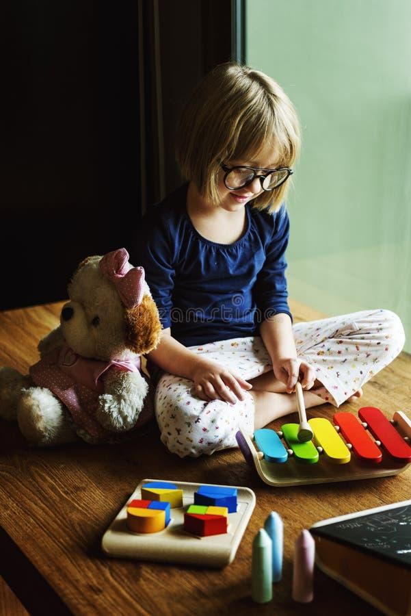 Ребенк играя игрушку ксилофона наслаждается концепцией стоковая фотография