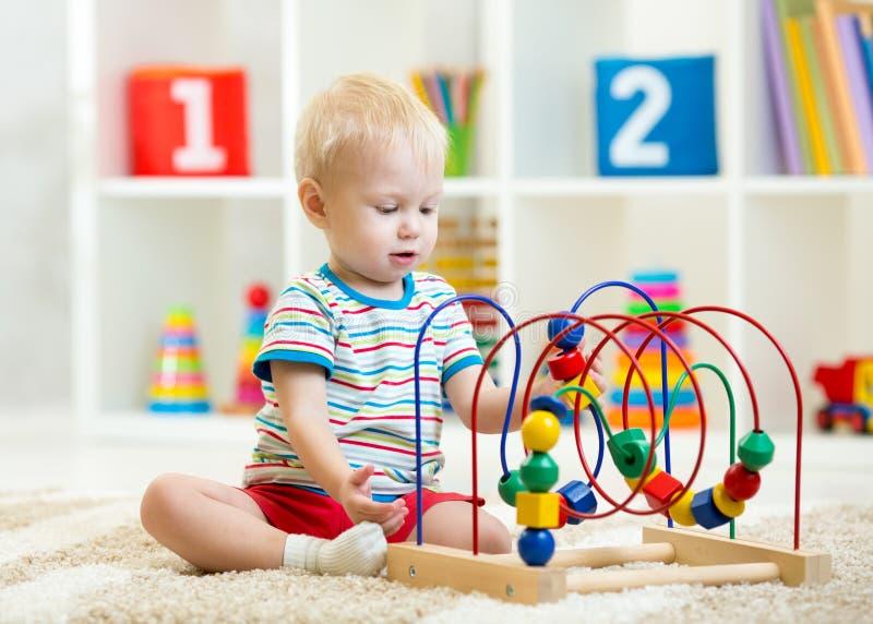 Ребенк играя с воспитательной игрушкой крытой стоковое изображение