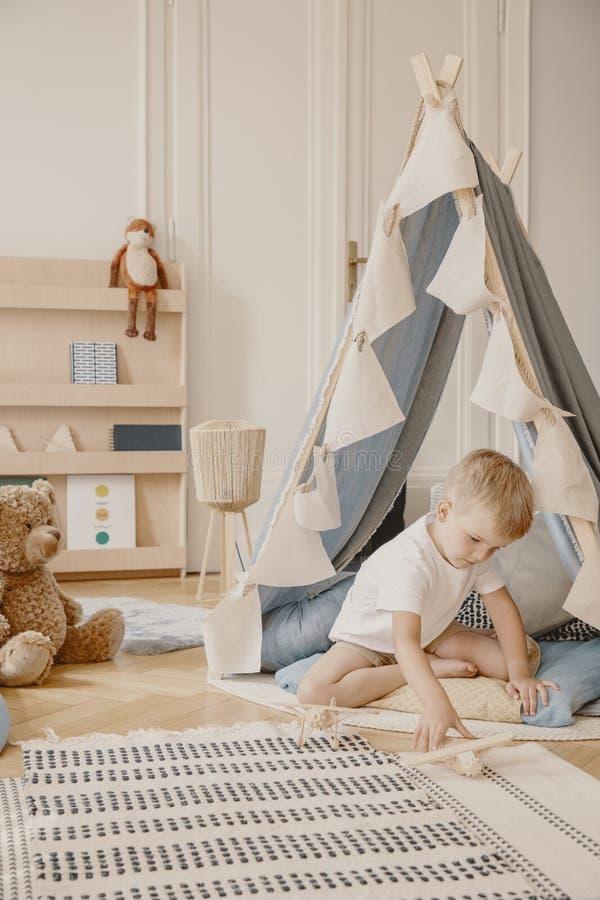 Ребенк играя с деревянным самолетом рядом с шатром в голубом интерьере игровой стоковые фото