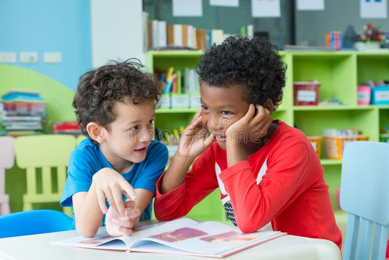 Ребенк 2 мальчиков сидит на таблице и книге сказа чтения в библиотеке preschool, концепции школьного образования детского сада стоковые изображения rf