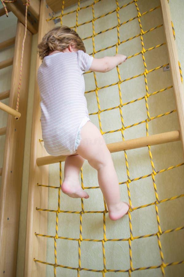 Ребенк младенца взбираясь лестница веревочки стоковые фото