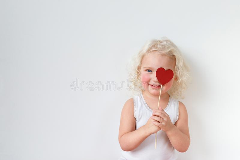 Ребенк наблюданный синью довольно малый одетый вскользь, имеет потеху внутри помещения, глаз крышек с ручкой сердца, радостной дл стоковое фото