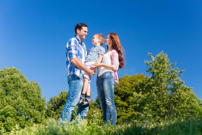 Ребенк нося семьи, родители стоя на луге стоковое изображение rf