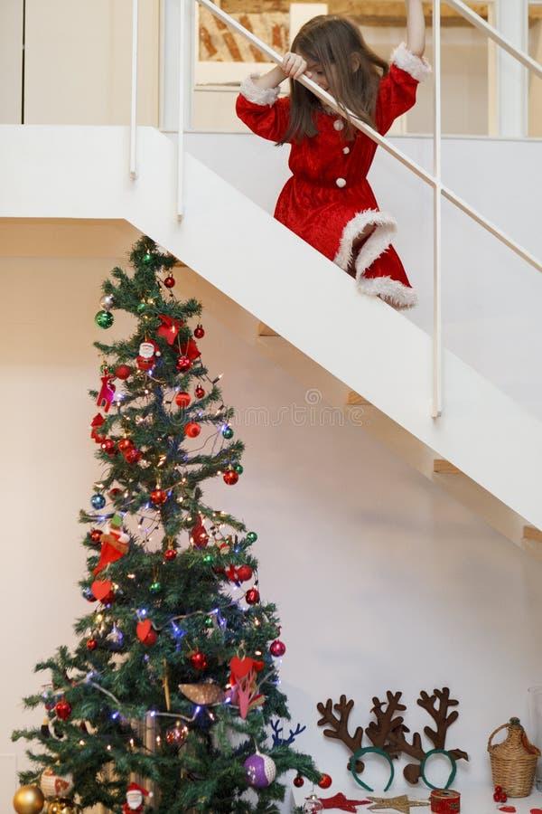 Ребенк одетый как santa идя вниз для подарков рождества стоковая фотография rf