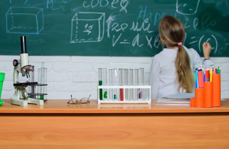Ребенк около предпосылки доски школы defocused Урок биологии школы Биология исследования ребенк с оборудованием в школе стоковое изображение