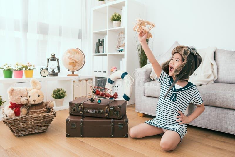 Ребенк поднимая ее самолет игрушки в воздухе стоковая фотография