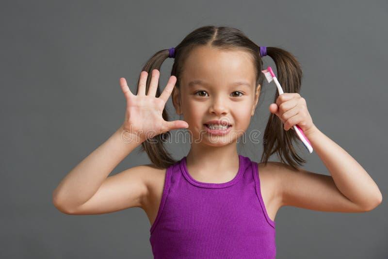 Ребенк показывая 5 пока держащ зубную щетку стоковое изображение