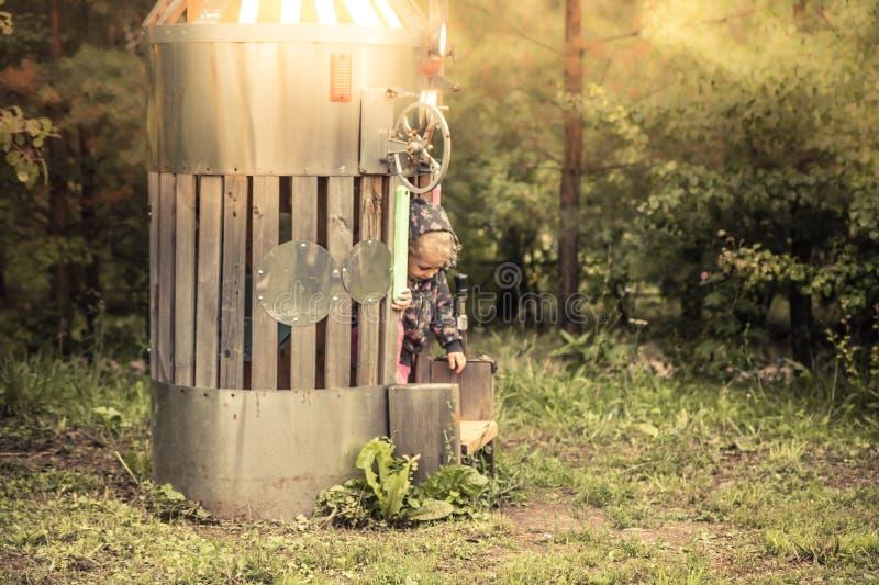 Ребенк ребенка играя в ракете космоса игрушки на спортивной площадке детей в парке лета при желтый солнечный свет символизируя ис стоковое изображение