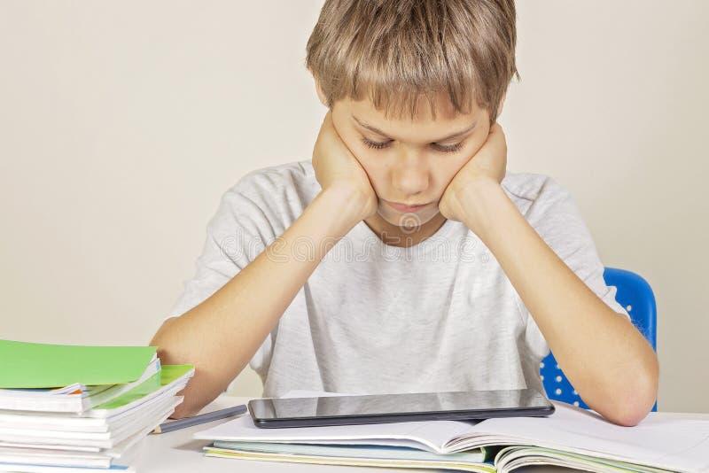 Ребенк сидя на таблице с тетрадями книг и используя планшет стоковые фото