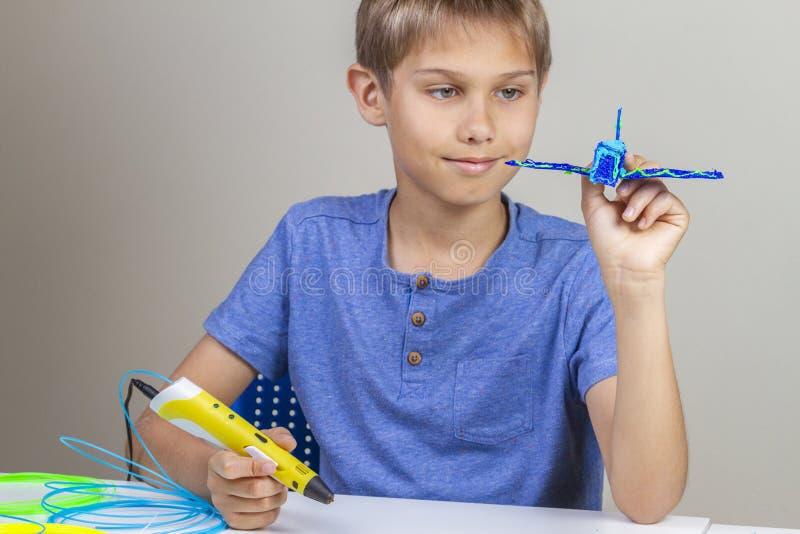 Ребенк создаваясь с ручкой печатания 3d и насладиться его новым голубым самолетом стоковые фотографии rf