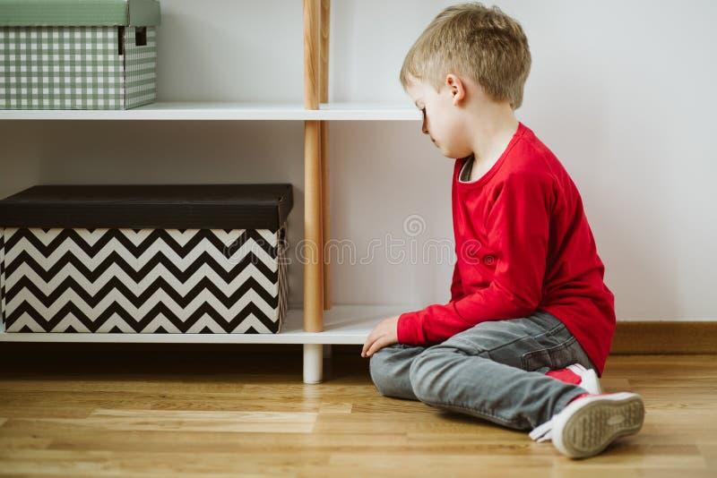 Ребенк с депрессией сидит в угле комнаты, и теряет интерес в деятельности и schoolwork стоковые фото