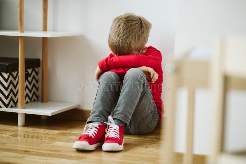 Ребенк с депрессией сидит в угле комнаты, и теряет интерес в деятельности и schoolwork стоковая фотография rf